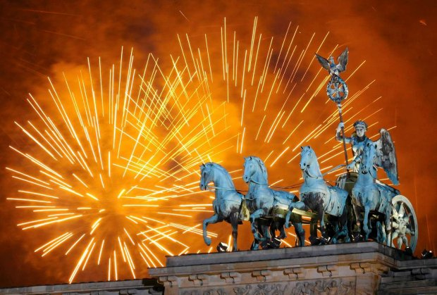 Fireworks light the sky above the Quadriga at the Brandenburg Gate in Berlin shortly after midnight, greeting the New Year, Sunday, Jan. 1, 2012. Hundred thousands of people celebrated the beginning of the New Year 2012 in Germany's capital. (AP Photo/Michael Sohn)